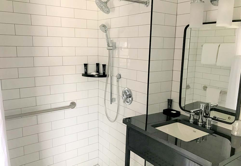 white subway tile shower in bathroom with back vanity