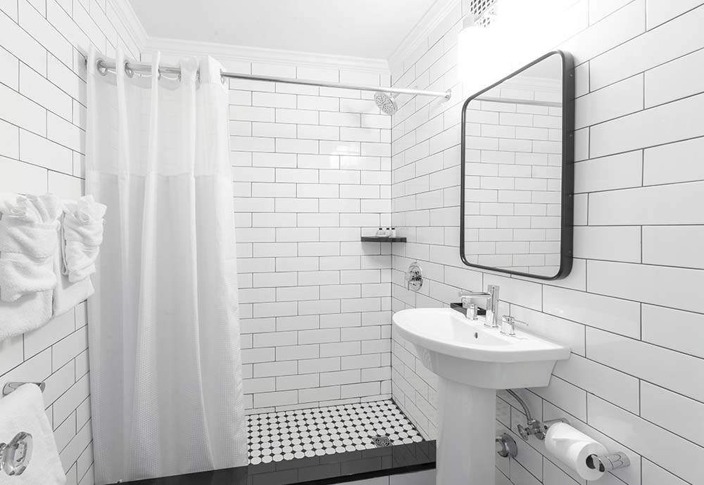 White titled bathroom with shower and sink
