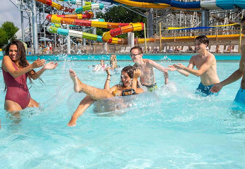 People splashing in pool at water park