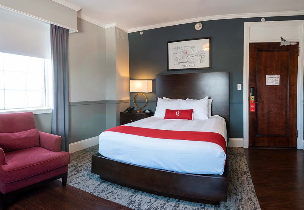 queen bed in modern styled hotel room with red chair