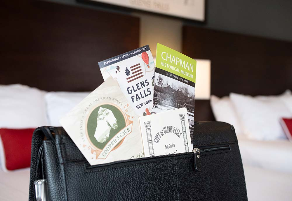 Area brochures sticking out of leather folder on bed
