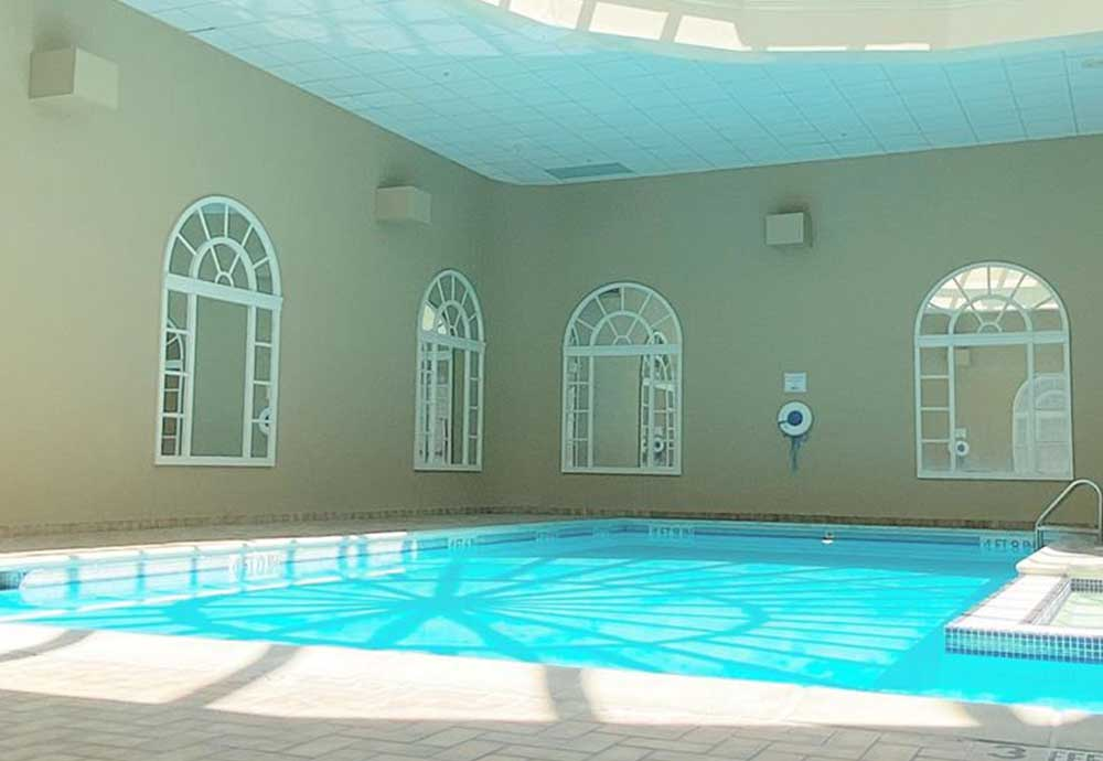 Indoor pool with sun coming through skylights