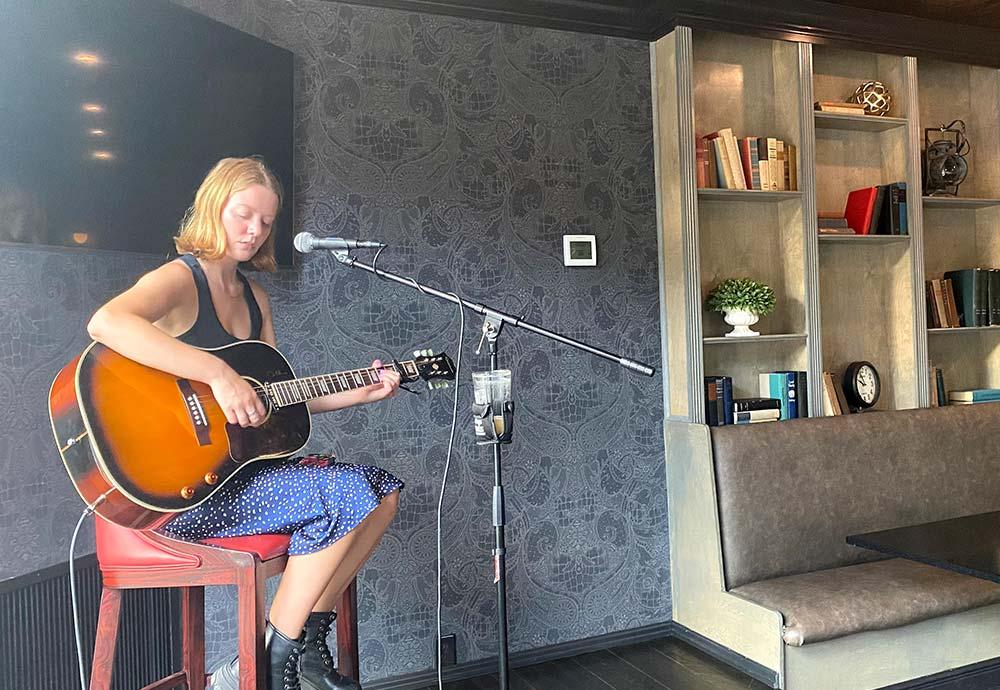 Women on stool playing guitar